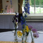 Single stemed flowers in vases clustered together